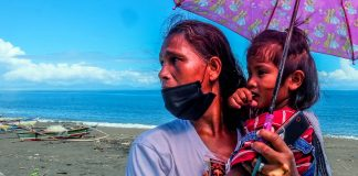 Annalisa Capa, 44, carries her three-year-old daughter on the shore of Baybay village in the town of Malinao, Albay. (Photo by Marielle Lucenio)