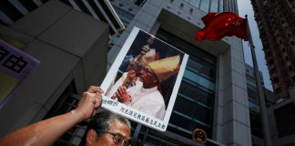 A protester carries a portrait of Bishop Su Zhi-ming of Baoding, Hebei province, who has been imprisoned in China and is now unreachable, during a protest demanding religious freedom outside China Liaison Office in Hong Kong July 11, 2012. (Reuters file photo)