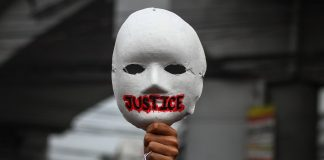 A activist raises a mask during an International Human Rights Day march in Manila on Dec. 10, 2020, to call for justice to alleged human rights abuses committed by state forces. (Photo by Jire Carreon)