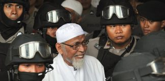 A file image of heavily armed police escorting radical cleric Abu Bakar Bashir (center) at South Jakarta prosecutor's office on Dec. 13, 2010 as the alleged spiritual leader of Indonesian jihad, or holy war, was transferred from prison. (Photo by Bay Ismoyo/AFP)