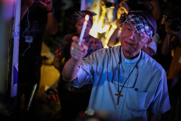 Bishop Broderick Pabillo, apostolic administrator of the Archdiocese of Manila, holds a candle during a demonstration in Manila in 2019. (Photo by Jire Carreon)