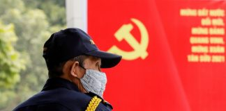 A security officer stands guard near a poster for the upcoming 13th National Congress of the ruling Communist Party of Vietnam, on a street in Hanoi, Vietnam Jan. 12. (Photos by Kham/Reuters)