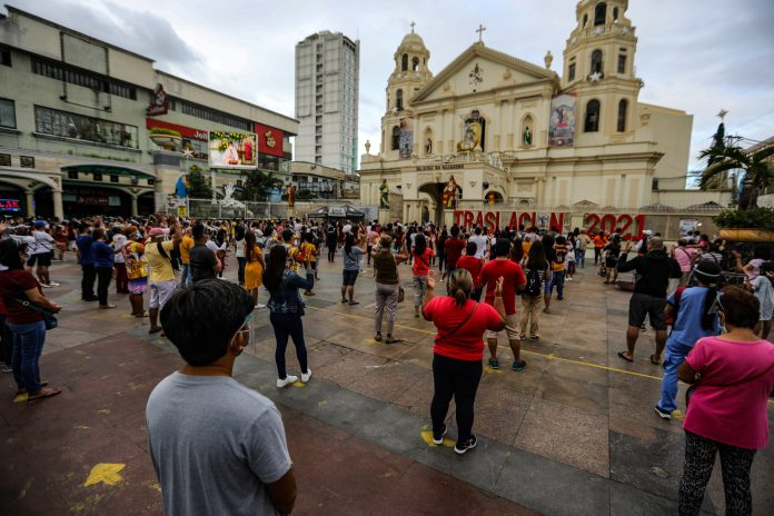 Devotees of the Black Nazarene stand outside the church in Manila's Quiapo district to hear Mass on Jan. 3, 2021. Mass gatherings, including religious services, are prohibited due to existing health protocols during the pandemic. (Photo by Jire Carreon)
