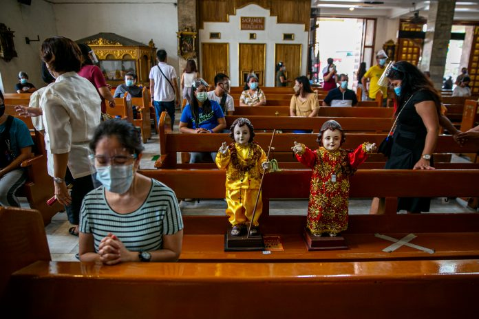 Images of the Santo Niño or the Child Jesus are brought to a church in Quezon City during its 'feast' on Jan. 17, 2021. (Photo by Mark Saludes)