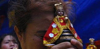A devotee of the Child Jesus holds an image of the Santo Niño while praying in the province of Cebu. (File photo by Victor Kintanar)