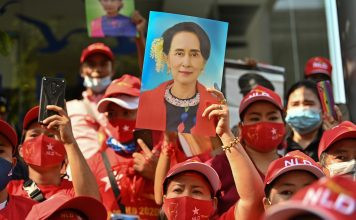 Myanmar migrants hold up portraits of Aung San Suu Kyi as they take part in a demonstration outside the Myanmar embassy in Bangkok on Feb. 1, after Myanmar's military detained the country's de facto leader Suu Kyi and the country's president in a coup. (Photo by Lillian Suwanrumpha/AFP)